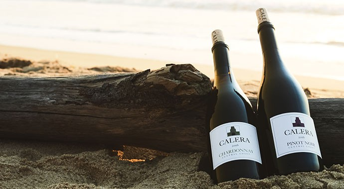 Two bottles of Calera in sand on the coast