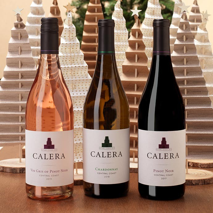 Three Calera Central Coast wines in front of paper Christmas trees