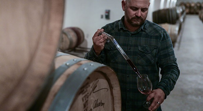 Winemaker Mike Waller in the cave tasting from barrels